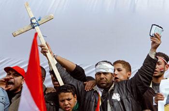 Un manifestante mostra un crocifisso e un Corano durante una manifestazione contro lo sgombero della piazza Tahrir due giorni dopo la caduta di Mubarak, domenica 13 febbraio 2011 [© Associated Press/LaPresse]